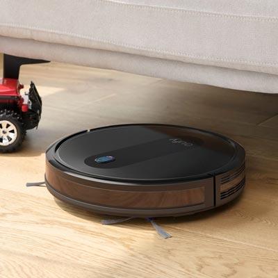 Robotstofzuiger Eufy Robovac 11s onder de bank aan het schoonmaken